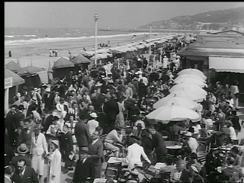 vidéos et rushes de b/w 1930s high angle pan crowded boardwalk + outdoor cafe alongside beach / deauville, normandy, france - station de vacances