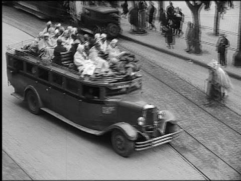 B/W 1930s high angle PAN crowded bus with people sitting on top driving on city street / Algiers, Algeria