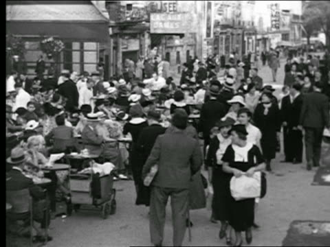 vidéos et rushes de b/w 1930s high angle pan from crowded sidewalk to crowded sidewalk cafe / paris, france - 1930