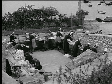 b/w 1930s high angle group of women in traditional dress at edge of basin scrub clothes / brittany, france - ブルターニュ点の映像素材/bロール