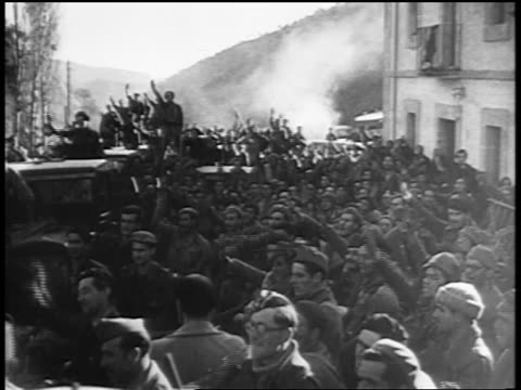 B/W 1930s high angle large group of soldiers on city street saluting someone offscreen / Spanish Civil War