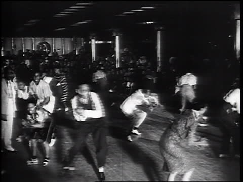 vidéos et rushes de b/w 1930s high angle male + female black swing dancers dancing near seated spectators in large room - rock