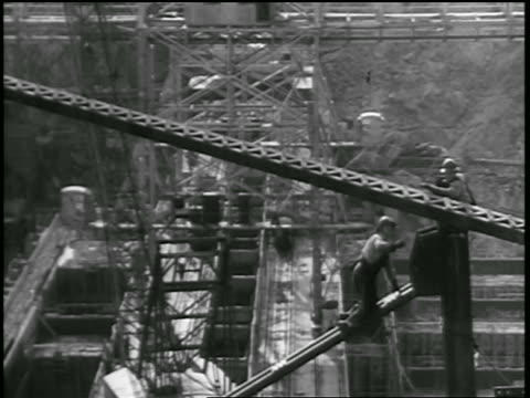 b/w 1930s high angle men working on beams at site of dam construction / documentary - 1930 stock videos and b-roll footage