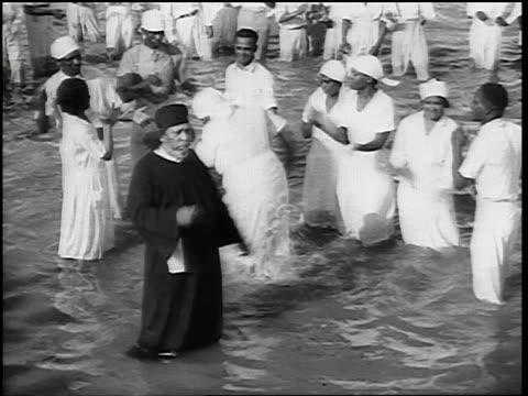 b/w 1930s high angle minister + group of black baptists dancing + singing knee-deep in water - バプテスト点の映像素材/bロール
