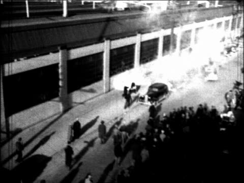 b/w 1930s high angle people running from throwing tear gas during auto strike / flint michigan - michigan stock videos & royalty-free footage