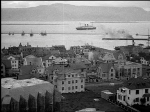 b/w 1930s high angle wide shot buildings of coastal town with cruise ship on water in background / norway - cruise stock videos and b-roll footage