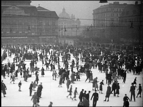 b/w 1930s high angle wide shot pan large crowd ice skating on outdoor rink / vienna, austria - ice skating stock videos & royalty-free footage