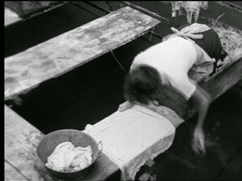 vidéos et rushes de b/w 1930s high angle woman scrubbing clothes on wooden plank over water (lake?) / normandy, france - 1930
