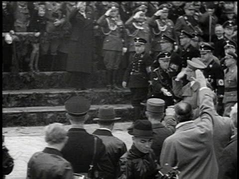 1930s hitler walking down street saluting crowd and fellow officers / germany - ゲシュタポ点の映像素材/bロール