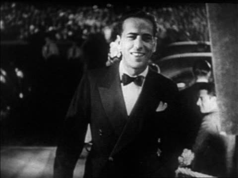 B/W 1930s Humphrey Bogart smiling at Hollywood premiere at Grauman's Chinese Theater / newsreel