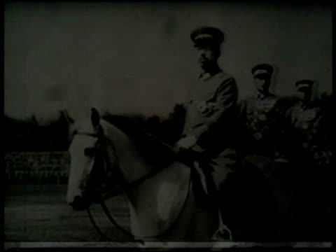 JAPAN RISE OF MILITARISM LA WS Emperor Showa Hirohito on white horse walking in front of others on horseback saluting VS Japanese soldiers one...
