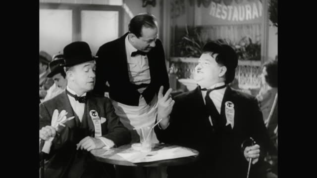 1930s laurel accuses hardy of hiding something from him - 1930 1939 stock-videos und b-roll-filmmaterial
