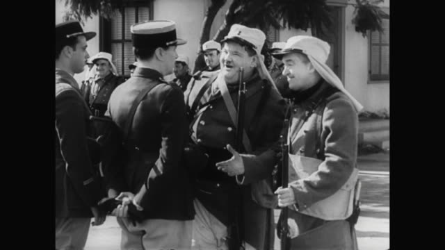 1930s laurel and hardy embarrass a man (reginald gardiner) in front of the soldiers - 1930 1939 stock-videos und b-roll-filmmaterial