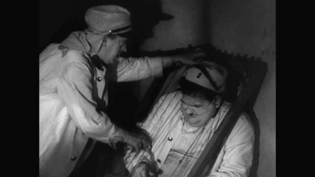 1930s laurel and hardy get stuck in a harp - 1930 1939 stock-videos und b-roll-filmmaterial