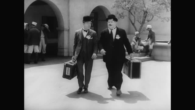 1930s laurel and hardy make a mess of a man's office when departing - 1930 1939 stock-videos und b-roll-filmmaterial