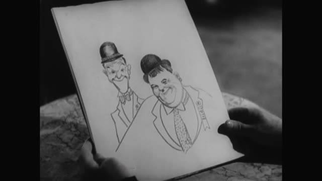 1930s laurel and hardy, while in a parisian cafe, have a sketch made of themselves - 1930 1939 stock-videos und b-roll-filmmaterial