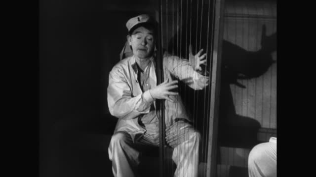 1930s laurel plays a makeshift harp in a jail cell - 1930 1939 stock-videos und b-roll-filmmaterial