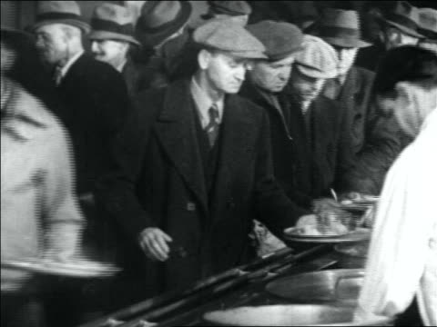B/W 1930s line of men being served food on dishes in soup kitchen / Great Depression