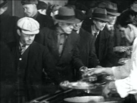 b/w 1930s line of men being served food on plates in soup kitchen / great depression - soup kitchen stock videos & royalty-free footage