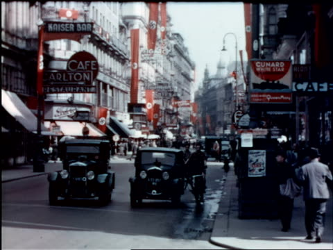 1930s long shot busy street w/traffic, cafes, red swastika flags / vienna, austria - 1930 1939点の映像素材/bロール