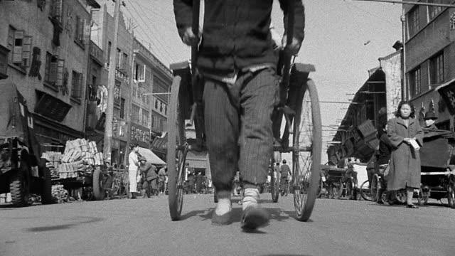 b/w 1930s low angle line of rickshaws + drivers passing over camera on street / asia - risciò video stock e b–roll