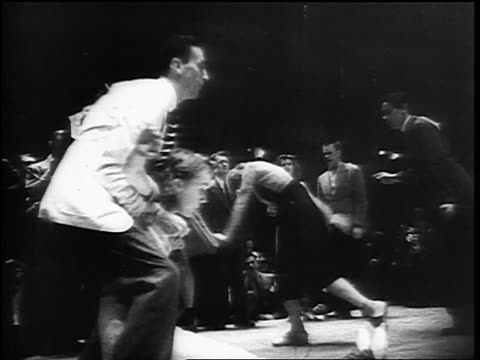 vidéos et rushes de b/w 1930s low angle male swing dancer with number on back catching + leapfrogging over female partner - couple d'adolescents