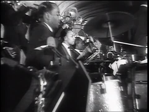 B/W 1930s low angle PROFILE male musicians playing trombones + trumpets in swing orchestra
