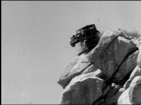 stockvideo's en b-roll-footage met b/w 1930s low angle tilt down car driving over cliff, flipping + landing in water - archiefbeelden