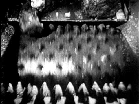 b/w cu 1930s machine breaking large rocks of coal into smaller pieces, maryland / usa - miniera di carbone video stock e b–roll