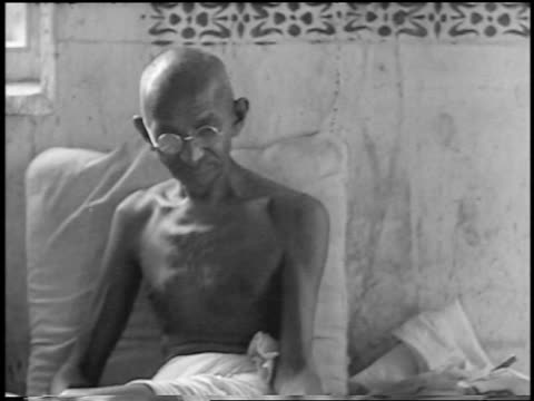 stockvideo's en b-roll-footage met 1930s mahatma gandhi sitting on bed without shirt on / newsreel - mahatma gandhi