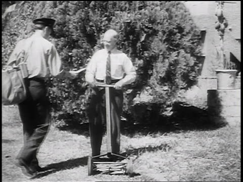 B/W 1930s mail carrier delivering mail to senior man mowing lawn / newsreel