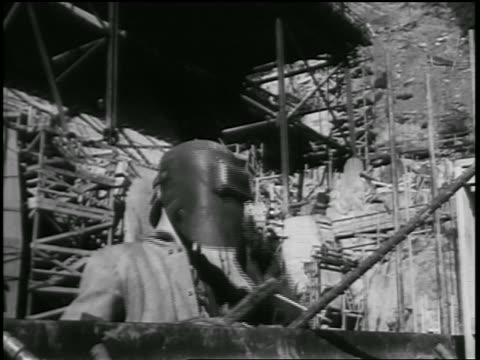 b/w 1930s male welder raising face helmet in dam construction / documentary - steel worker stock videos & royalty-free footage