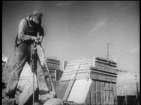 b/w 1930s male worker using tool in dam construction / tennessee river valley - new deal video stock e b–roll