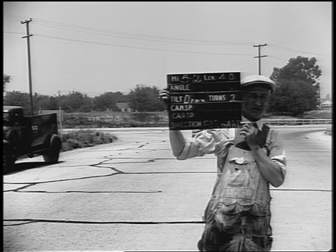 b/w 1930s man holding slate between takes in movie making / car passes on road in background - film slate stock videos & royalty-free footage
