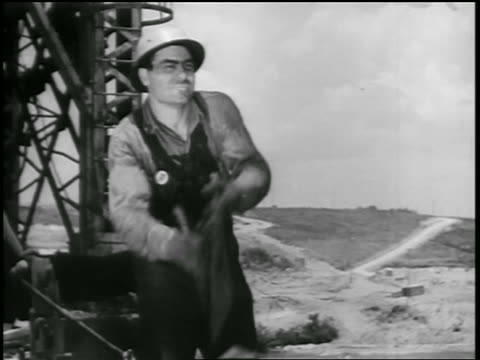 b/w 1930s man in hard hat throwing something off screen at site of dam construction / documentary - one mid adult man only stock videos & royalty-free footage