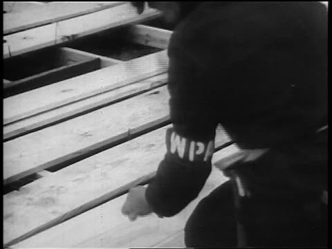 b/w 1930s man in wpa armband hammering wood outdoors during great depression - 雇用促進局点の映像素材/bロール