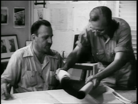 B/W 1930s man laying blueprints on other man's desk / documentary