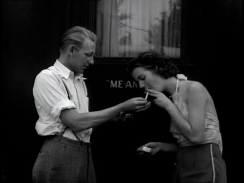 stockvideo's en b-roll-footage met 1930s ms man lighting a woman's cigarette with matches / miami, florida, united states - 1930