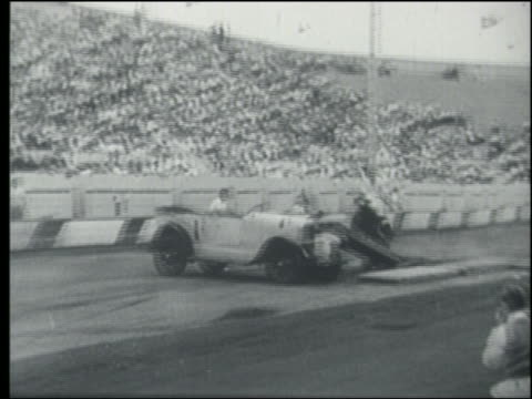 b/w pan 1930s man on motorcycle doing jump over car in crowded stadium - stunt person stock videos & royalty-free footage