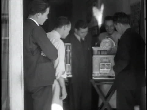 1930s ms man putting money into a slot machine and people watching / miami, florida, united states - man and machine stock videos & royalty-free footage