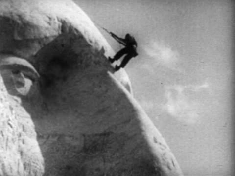1930s man rappelling down nose of george washington on mt. rushmore / south dakota / newsreel - male likeness stock videos & royalty-free footage