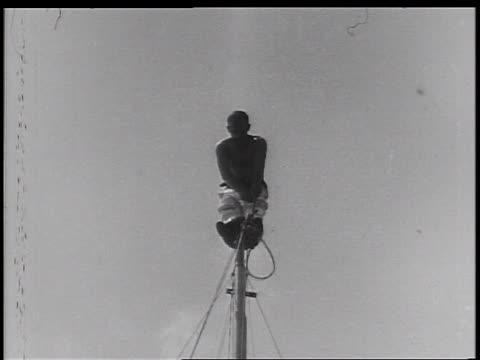 b/w 1930s man sitting on flagpole removing his pants / newsreel - fahnenstange stock-videos und b-roll-filmmaterial