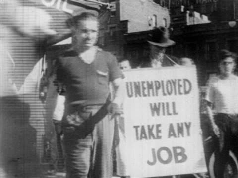 b/w 1930s man walking on busy city sidewalk carrying sign that reads unemployed will take any job - disoccupazione video stock e b–roll