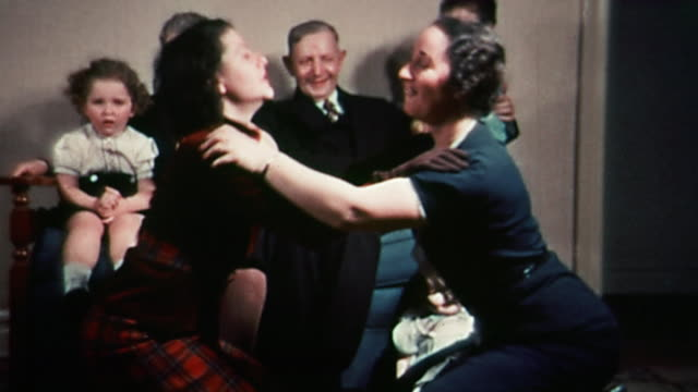 1930s medium shot 2 young women bobbing heads, hugging and making faces on floor / family in background - bizarre stock videos & royalty-free footage