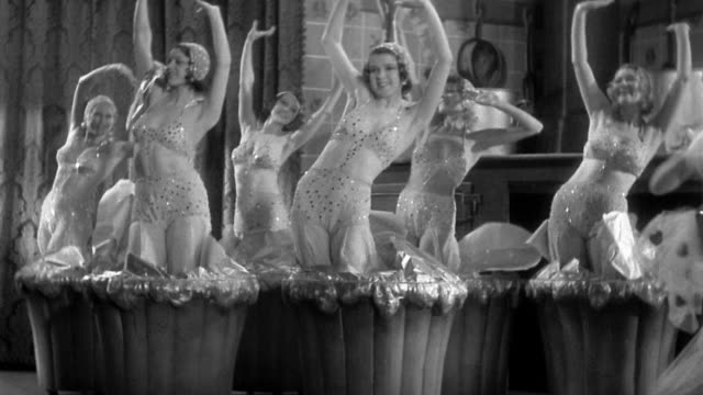 1930s medium shot group of showgirls bursting out of giant cupcakes in kitchen / one woman dancing
