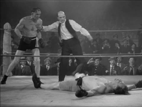 1930s medium shot opponents in boxing match / one boxer knocked out / referee counting - 30 39 years stock videos & royalty-free footage
