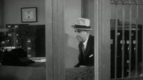 vidéos et rushes de 1930s medium shot tracking shot male bank robber holding up bank tellers, stuffing money into handbag and exiting - braqueur de banque