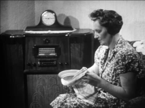 stockvideo's en b-roll-footage met b/w 1930s middle-aged woman sitting + listening to radio while drying plate / educational - 1930