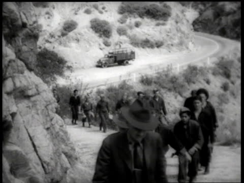 1930s migrant workers walking up hill, following officials in suits / united states - lavoratore emigrante video stock e b–roll