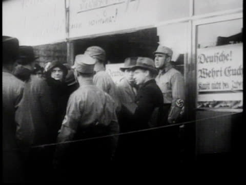1930s montage antisemitic signs in berlin with brown shirts on street corners / germany - ナチズム点の映像素材/bロール